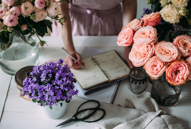 Hände eines floristen, der in ein notizbuch schreibt