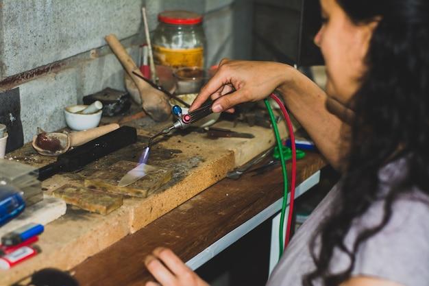 Hände eines handwerklichen juweliers, der eine lötlampe hält. juwelen und gegenstände von goldschmiedewerkstatt.