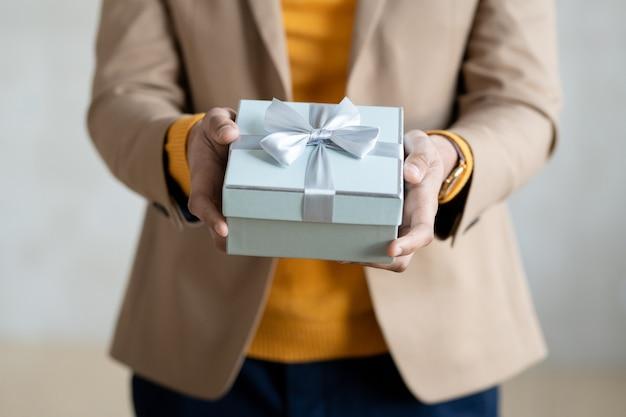 Hände eines jungen eleganten geschäftsmannes mit verpacktem geburtstagsgeschenk in einer geschenkbox, die ihnen ein geschenk in einer blauen box mit einer schleife aus seidenband überreicht