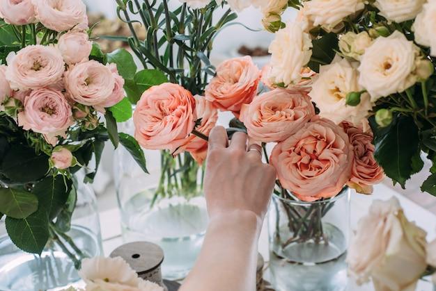 Hände eines jungen floristen, der einen blumenstrauß schafft
