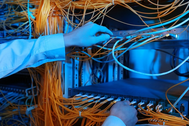 Hände eines jungen ingenieurs, der kabel im serverraum anschließt