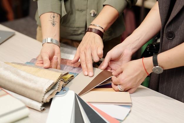 Hände eines jungen managers des studios des innenarchitektur-beratungskunden, während beide neue textilmuster für möbel durchsehen