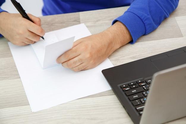 Hände eines jungen mannes, der auf ein blatt papier schreibt