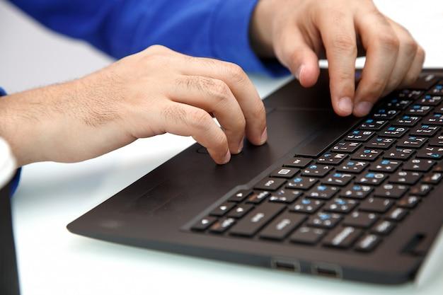 Hände eines jungen mannes, der auf einem laptop schreibt. der blick von oben