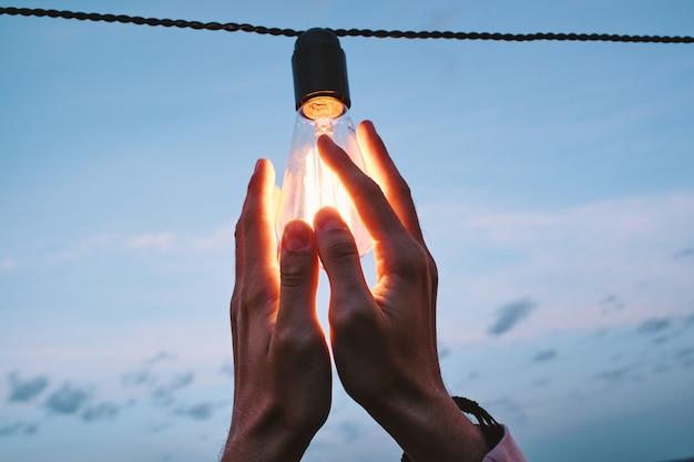 Hände eines jungen mannes, der eine am draht hängende glühbirne hält