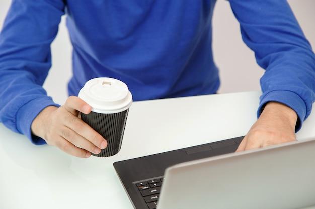 Hände eines jungen mannes, der kaffee und druck auf einem laptop hält