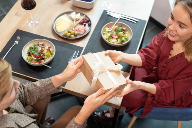 Hände eines jungen mannes, der seiner hübschen freundin eine geschenkbox mit weißem seidenband übergibt, während beide am bedienten tisch sitzen und zusammen zu abend essen