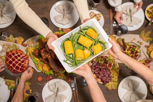 Hände eines jungen mannes, der seiner mutter eine schüssel mit gebackenem mais und grünen bohnen über einen festlichen tisch reicht, der zum thanksgiving-familienessen serviert wird?
