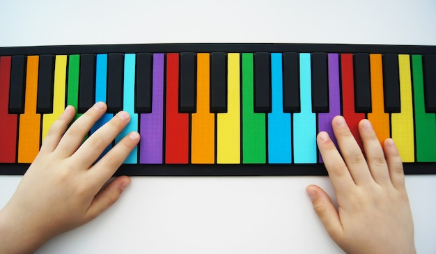 Hände eines kindes, das auf einem flexiblen bunten klavier für kinder spielt. isoliert auf einer weißen wand
