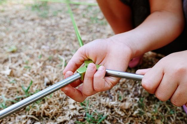 Hände eines kindes, das die stangen eines zeltes verbindet, um es anzubringen.