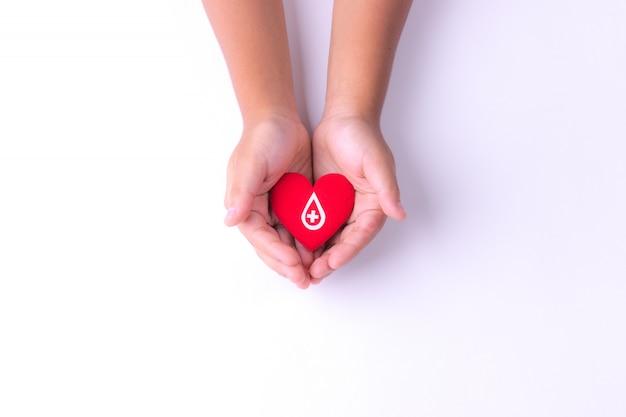 Hände eines kindes, die rotes herz für blutspende halten