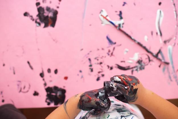 Hände eines kleinen jungen, der mit aquarellen auf rosa papierblatt malt. kleiner junge mit einem pinsel und farben.