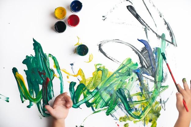Hände eines kleinen jungen, der mit aquarellen auf weißbuchblatt malt. kleiner junge mit einem pinsel und farben.
