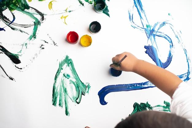 Hände eines kleinen jungen, der mit aquarellen auf weißbuchblatt malt.