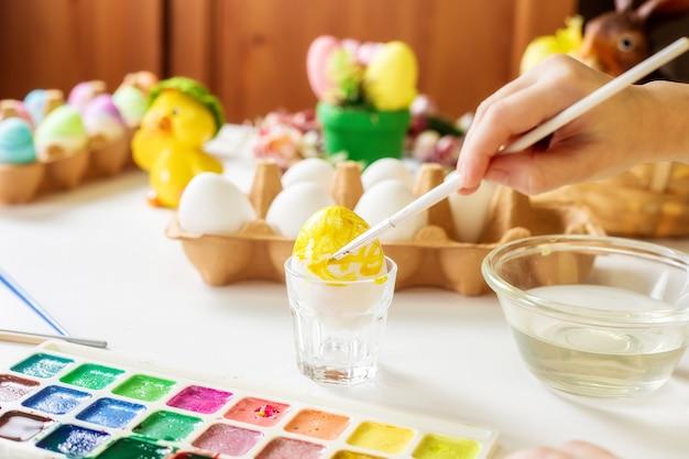 Hände eines kleinen mädchens malen eier mit wasserfarben für ostern.