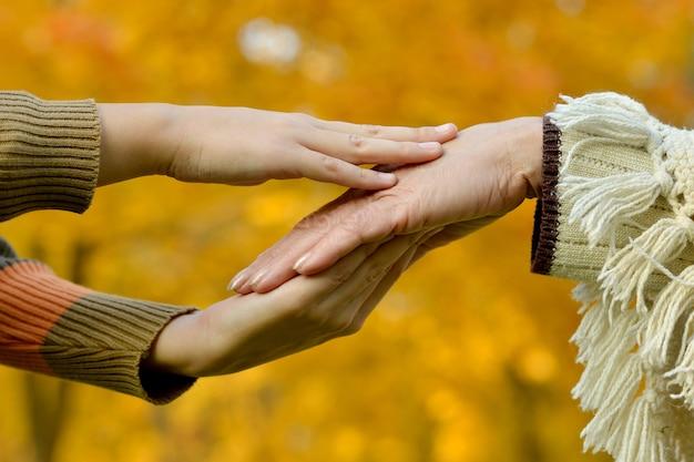 Hände eines liebevollen paares auf einem hintergrund von herbstblättern