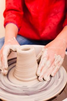 Hände eines mädchens, das versucht, auf einer töpferscheibe keramik aus weißem ton herzustellen