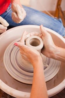 Hände eines mädchens, das versucht, mit einem lehrer auf einer töpferscheibe keramik aus weißem ton herzustellen