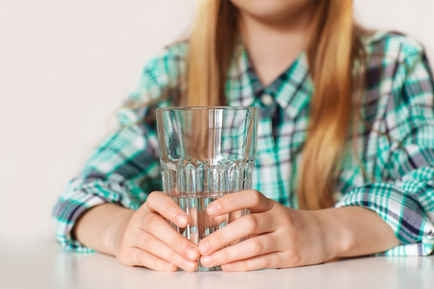 Hände eines mädchens hautnah, hält ein glas reines wasser