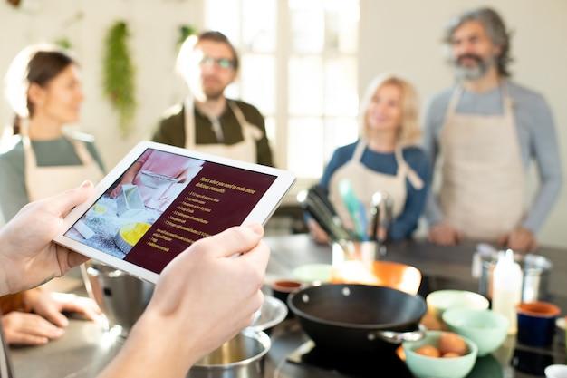 Hände eines männlichen kochtrainers mit tablet, der das online-rezept köstlicher hausgemachter croissants gegen eine gruppe seiner auszubildenden durchsieht