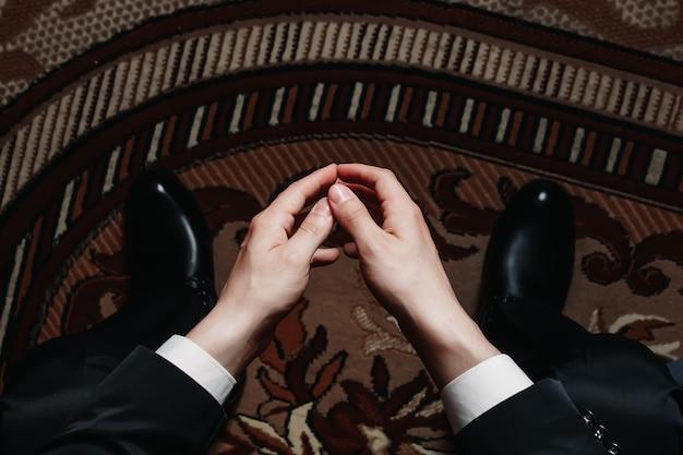 Hände eines mannes auf einem hintergrund von schuhen