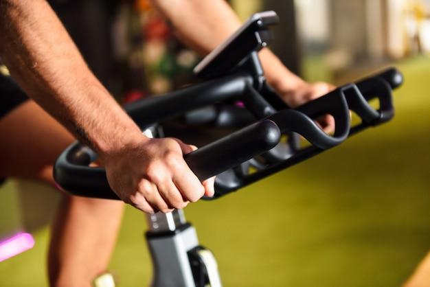 Hände eines mannes, der an einer turnhalle tut, die das cyclo innen tut.