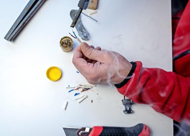 Hände eines mannes, der drähte für reparaturen löt