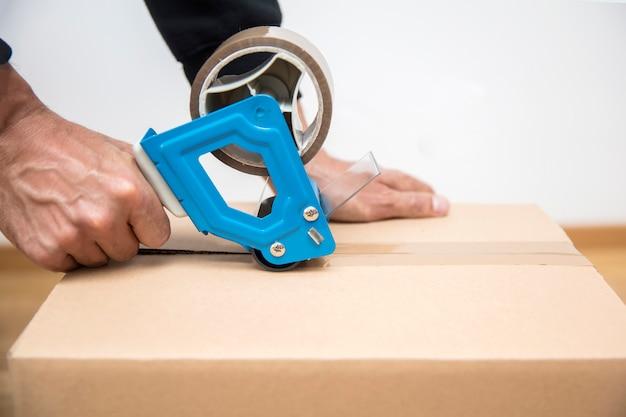 Hände eines mannes, der einen bandspender verwendet, um einen versandkarton zu versiegeln