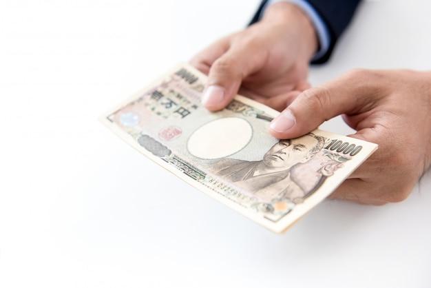 Hände eines mannes, der geld der japanischen yen in der form von banknoten gibt