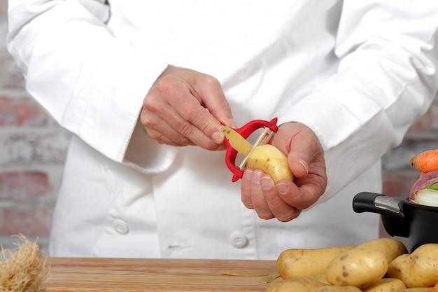 Hände eines mannes, der kartoffel mit peeler abzieht
