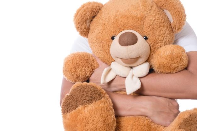 Hände eines mannes, die braunen netten flaumigen teddybären als geschenk halten