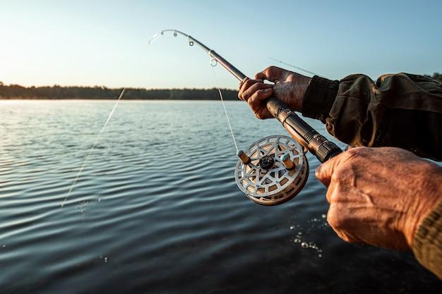 Hände eines mannes in einem urp-plan halten eine angelrute, ein fischer fängt fische an der dämmerung, die hobbyferien fischt