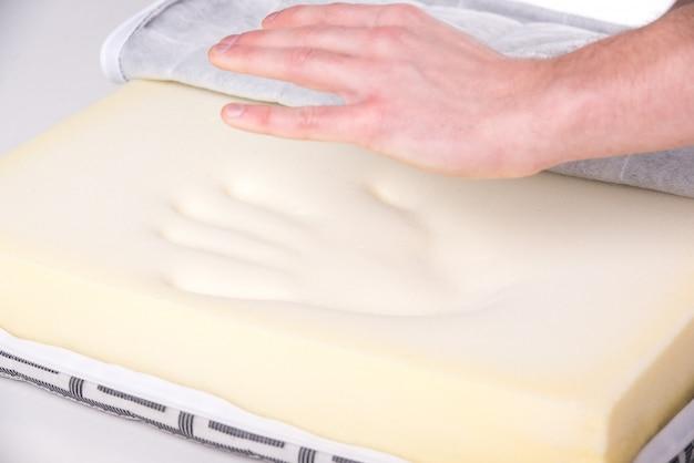 Hände eines mannes mit einer schönen matratze, die sie beim schlafen unterstützt.