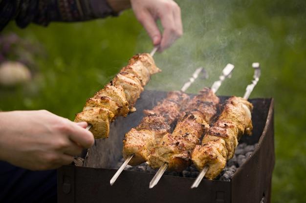 Hände eines mannes verdrehen spieße mit fleisch auf einem barbecue-grill