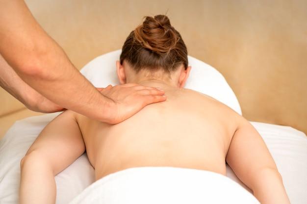 Hände eines masseurs, der rücken einer jungen erwachsenen frau im spa-salon massiert