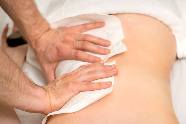 Hände eines masseurs mit handtuchmassage zurück einer jungen erwachsenen frau im spa-salon
