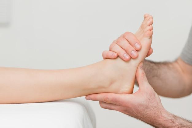 Hände eines osteopathen, der einen fuß massiert