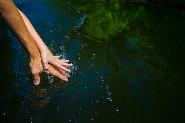 Hände eines paares im wasser stecken