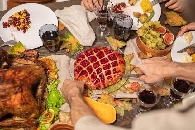 Hände eines reifen mannes mit scharfem messer, das leckeren hausgemachten kuchen mit himbeermarmelade zwischen frischen früchten, gebratenem truthahn und getränken auf dem tisch schneidet