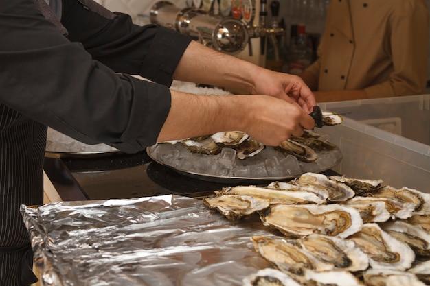 Hände eines restaurantkochs, der in der küche drinnen gerichte und snacks mit austern zubereitet