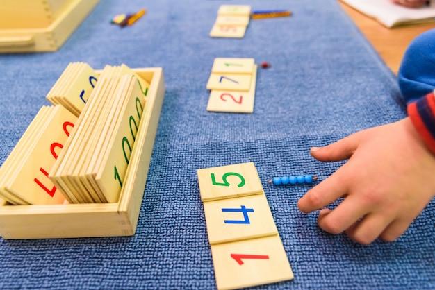 Hände eines studentenjungen, der hölzernes material in einer montessori-schule verwendet.
