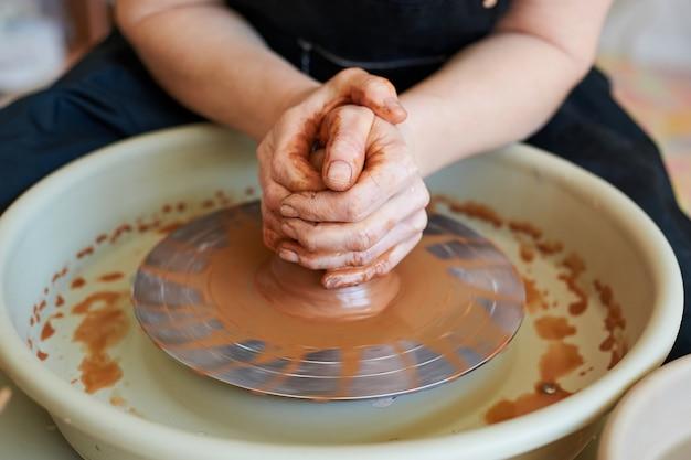 Hände eines töpfermeisters, der beginn der herstellung von tonprodukten. handwerksproduktion in der werkstatt.