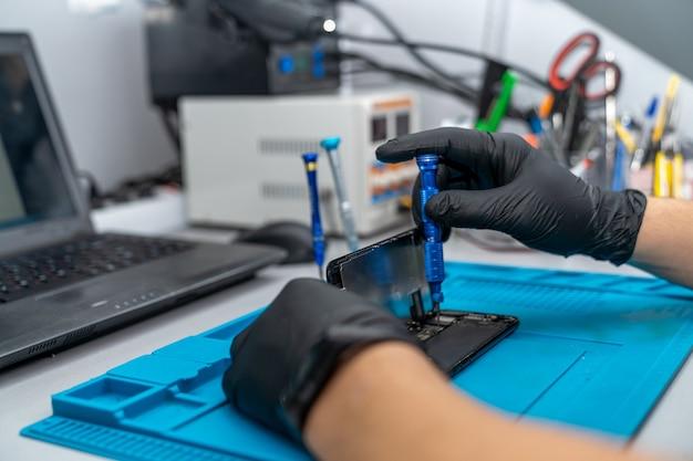 Hände eines vorarbeiters, der ein handy repariert