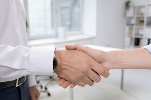 Hände erfolgreicher geschäftspartner gratulieren einander per handschlag zu einem neuen geschäft