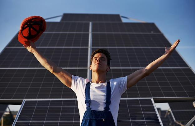 Hände erhoben. männlicher arbeiter in blauer uniform im freien mit solarbatterien am sonnigen tag.