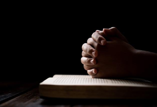 Hände frau, die auf der bibel liegt, während sie für den segen der christlichen religion betet und zu gott betet