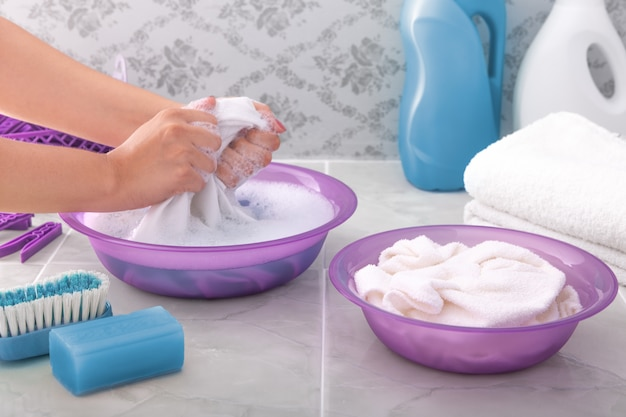 Hände frau wäscht kleidung von hand in seifigem wasser.
