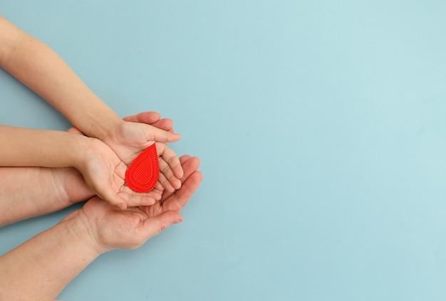 Hände frauen halten blutstropfen auf blauem hintergrundkonzept der blutspende bluttransfusion