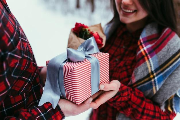 Hände geben eine geschenkbox mit band. unscharfer hintergrund.
