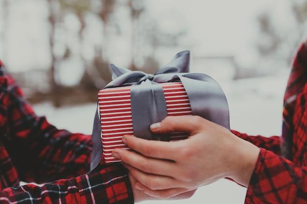 Hände geben eine geschenkbox mit band.